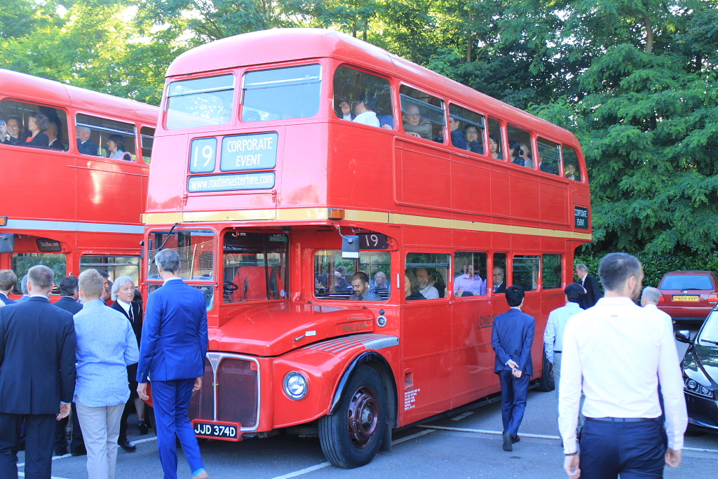 guests walking around red routemaster hire london bus
